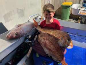 Little kid Mason holding two large snapper fish